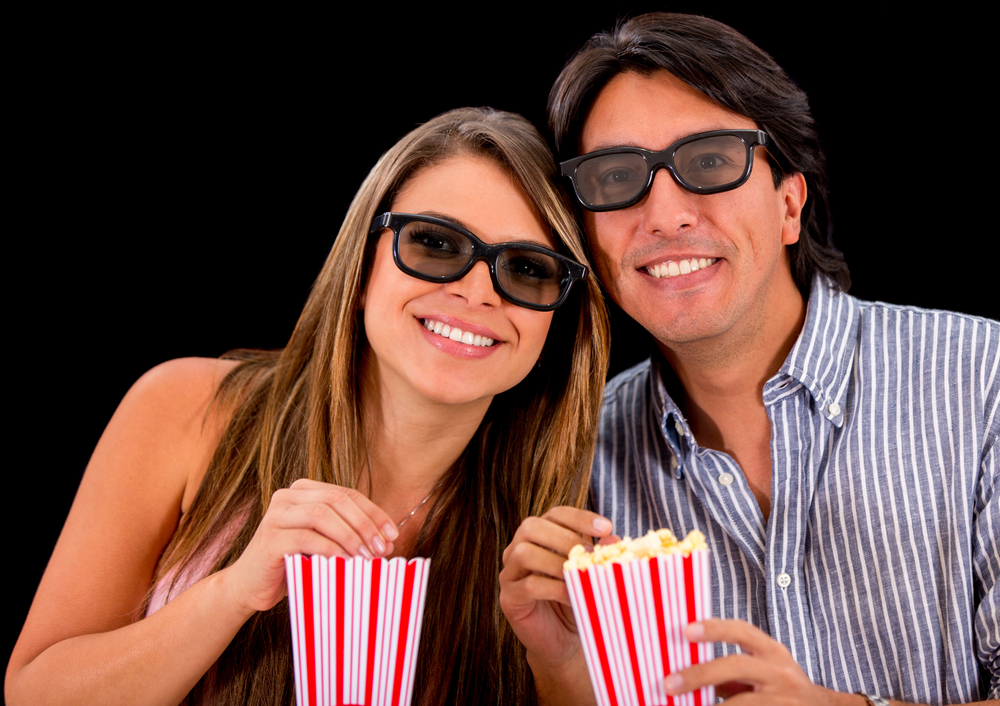 Happy couple watching a 3D movie and wearing glasses